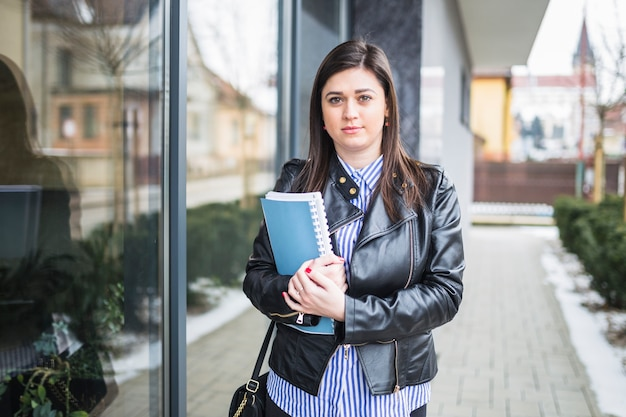 Portrait of a young businesswoman with books