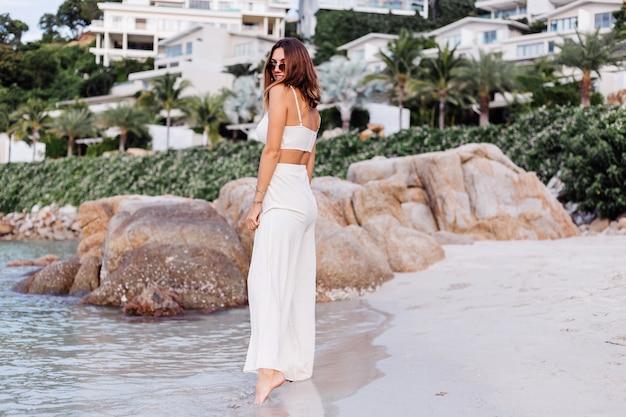 Ritratto di giovane donna calmo felice indoeuropeo in forma sottile in top crop cami e pantaloni da solo sulla spiaggia tropicale rocciosa al tramonto