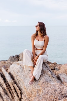 Portrait of young calm happy caucasian fit slim woman in crop cami top and pants set sits alone on rocky tropical beach at sunset