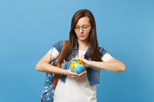 Portrait of young calm woman student in glasses with backpack hold looking down on world globe isolated on blue background. education in college. save planet. ecology environment protection concept.