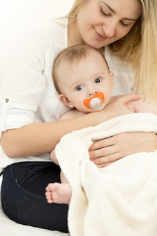 Portrait of young caring mother sitting on bed and holding baby on hands