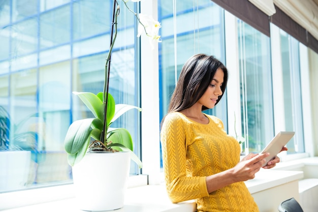 Portrait of a young casual businesswoman using tablet computer in office near window