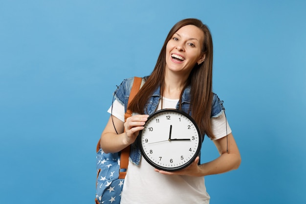 Portrait of young casual laughing pleasant woman student in t-shirt, denim clothes with backpack holding alarm clock isolated on blue background. education in university. copy space for advertisement.