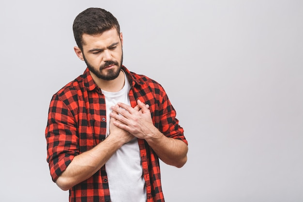 Portrait of a young casual man standing isolated over white background, having a heart attack. heartache.