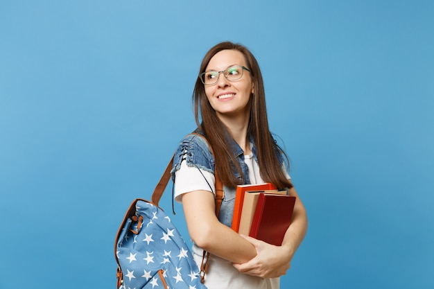 Portrait of young casual pretty woman student in glasses with backpack looking aside on copy space holding school book isolated on blue background. education in high school university college concept.