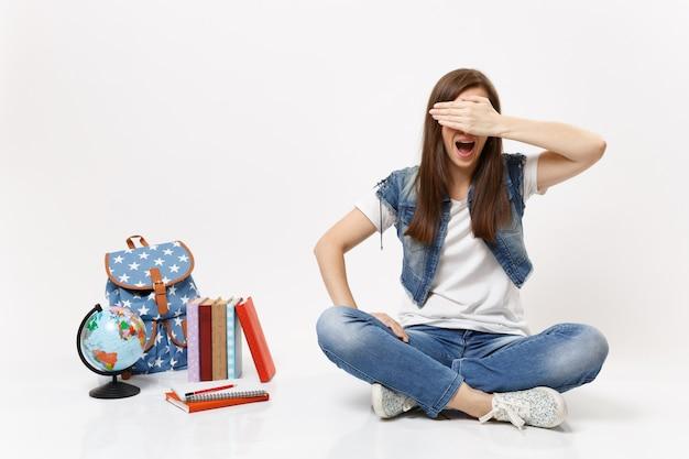 Ritratto di giovane studentessa casual che urla coprendosi il viso con la mano e si siede vicino a libri di scuola zaino del globo isolati