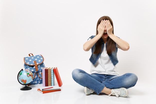 Ritratto di giovane studentessa casual con la bocca aperta che copre il viso con le mani, seduta vicino al globo, zaino, libri scolastici isolati
