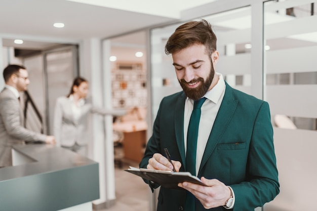 Portrait of young caucasian bearded businessman in suit standing at hallway and writing something on the clipboard.