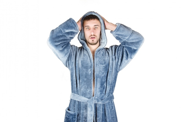 Portrait of young caucasian bearded man in blue bathrobe shows confused face emotion isolated