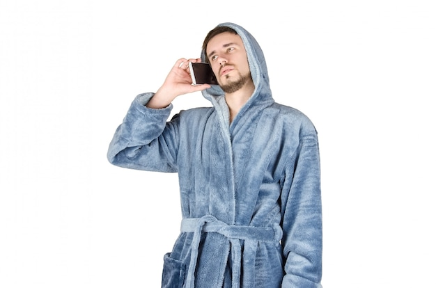 Portrait of young caucasian bearded man in blue bathrobe talks on smartphone isolated on white background