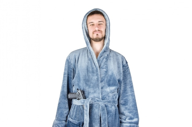 Portrait of young caucasian bearded man in blue bathrobe with black firearm isolated