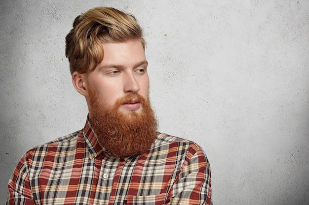Ritratto di giovane uomo brutale caucasico con barba sfocata che indossa camicia a scacchi rossa che guarda lontano con espressione pensierosa.