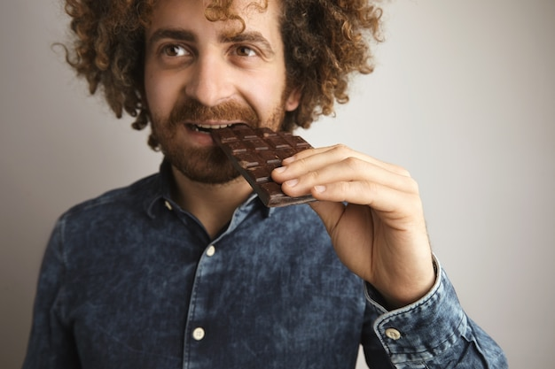 Portrait of young caucasian curly hair happy man with healthy skin bites organic freshly baked chocolate bar with side of mouth, looking in side of camera