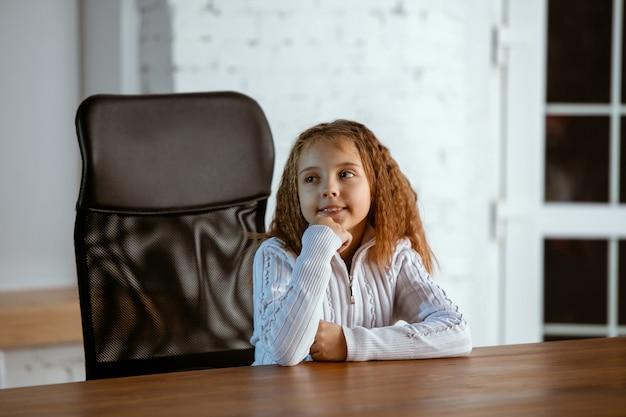 Ritratto di giovane ragazza caucasica in abiti casual sembra sognante, carino e felice. guardando in alto e pensando, seduto al tavolo di legno in casa. concetto di futuro, obiettivo, sogni, visualizzazione.