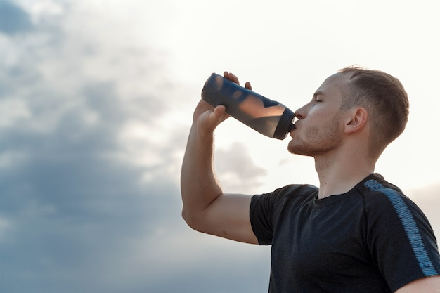 Portrait of a young caucasian guy in a black t-shirt and black shorts drinking water from a bottle