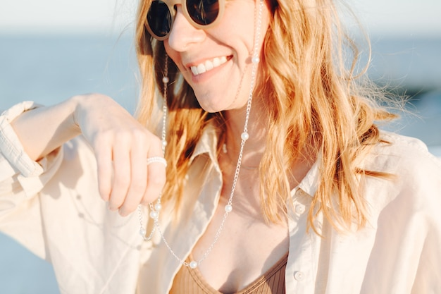 Portrait of young caucasian laughing smiling girl woman in sunglasses outdoors on the beach background.
