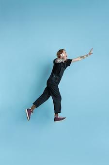 Ritratto di giovane uomo caucasico sembra sognante, carino e felice. saltando. ridendo su sfondo blu studio. copyspace per la tua pubblicità. concetto di futuro, obiettivo, sogni, visualizzazione.