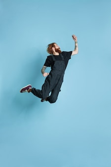 Portrait of young caucasian man looks dreamful, cute and happy. jumping. laughting on blue studio background. copyspace for your advertising. concept of future, target, dreams, visualisation.
