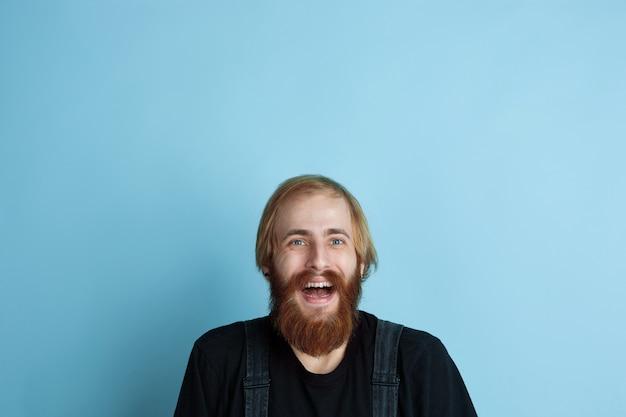 Ritratto di giovane uomo caucasico sembra sognante, carino e felice. guardando in alto e pensando allo spazio blu