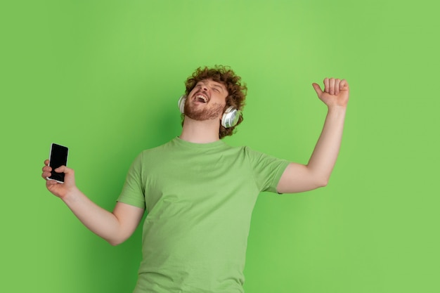 Portrait of young caucasian man with bright emotions on green studio