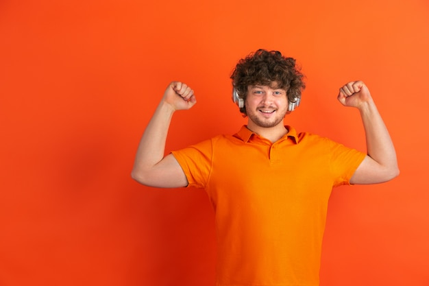 Portrait of young caucasian man with bright emotions on orange studio