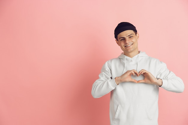 Portrait of young caucasian man with bright emotions on pink studio background