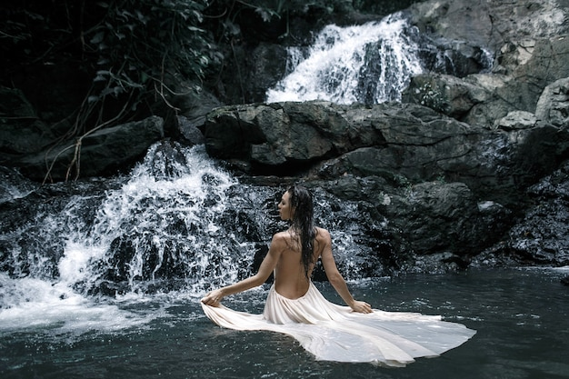 Portrait of the young caucasian woman enjoying in front of a waterfall in an white evening dress. back view