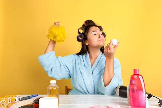 Portrait of young caucasian woman in her beauty day, skin and hair care routine. female model with natural cosmetics applying cream and oils for make up. body and face care, natural beauty concept.