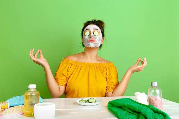 Ritratto di giovane donna caucasica nella sua routine di cura di bellezza, pelle e capelli. modello femminile con cosmetici naturali che applicano maschera facciale per il trucco. cura del viso e del corpo, concetto di bellezza naturale.