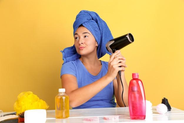 Ritratto di giovane donna caucasica nella sua routine di cura di bellezza, pelle e capelli