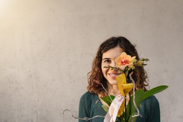 카메라를보고 세로 젊은 백인 여자 눈 앞에서 노란 난초 식물 미소.