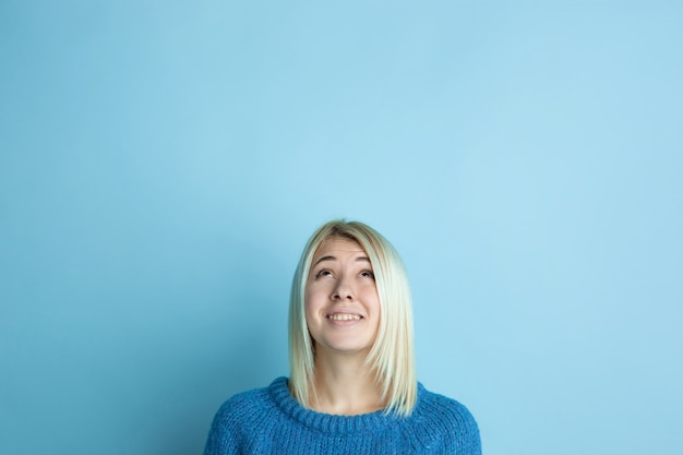 Portrait of young caucasian woman looks dreamful, cute and happy