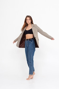 Portrait of young caucasian woman with long hair in black top, blue jeans and suit jacket on white studio. pretty girl posing with bare feet