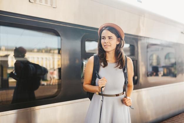 Portrait young caucasian woman with toothy smile standing at train station train