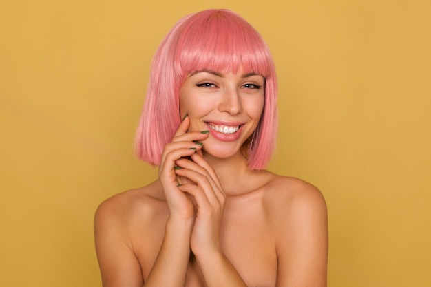 Portrait of young charming blue-eyed pink haired female touching gently her face with raised hands and looking cheerfully  with broad sincere smile, isolated over mustard wall