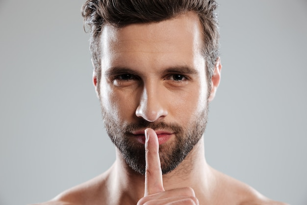 Portrait of a young charming naked man showing silence gesture