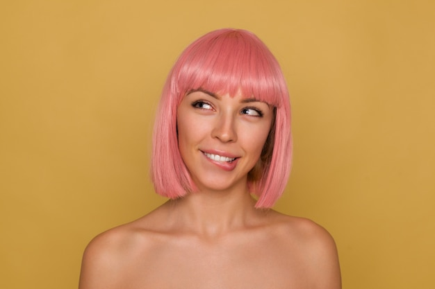 Portrait of young charming positive lady with pink trendy bob hairstyle looking dreamily aside and biting her underlip, squinting her blue eyes while posing over mustard background