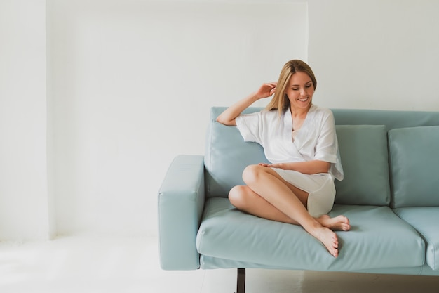 Portrait of a young charming woman in a silk robe at home on the sofa