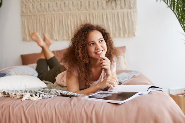Ritratto di giovane signora afroamericana allegra con i capelli ricci, si trova sul letto e legge una rivista, sorride in generale, gode di una giornata di sole libero e distoglie lo sguardo sognante.