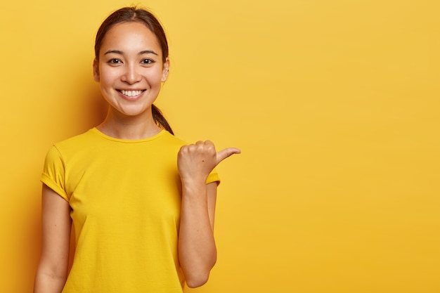 Portrait of young cheerful asian female points away with thumb, happy face expression, demonstrates copy space for advertisement, has pleasant appearance, wears bright yellow clothes.