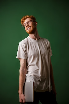 Portrait of young cheerful bearded readhead hipster, holding laptop, looking away