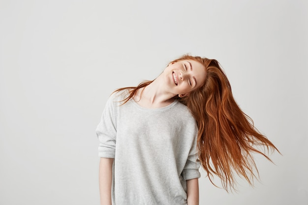 Portrait of young cheerful beautiful redhead girl smiling with closed eyes shaking head and hair .
