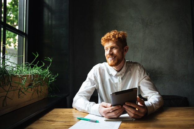 Portrait of young cheerful ginger bearded man, sitting at wooden table, holding tablet, looking at window