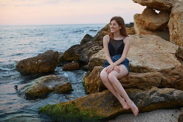 Ritratto di giovane donna carina allo zenzero allegro con le lentiggini si siede sulla spiaggia, distoglie lo sguardo sognante e sorride, sembra positivo e felice.