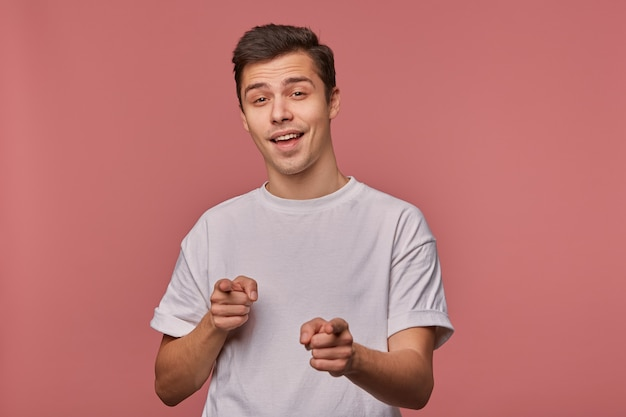 Il ritratto di giovane ragazzo allegro indossa in maglietta vuota, punta con le dita, si leva in piedi sul rosa e ampiamente sorridente.