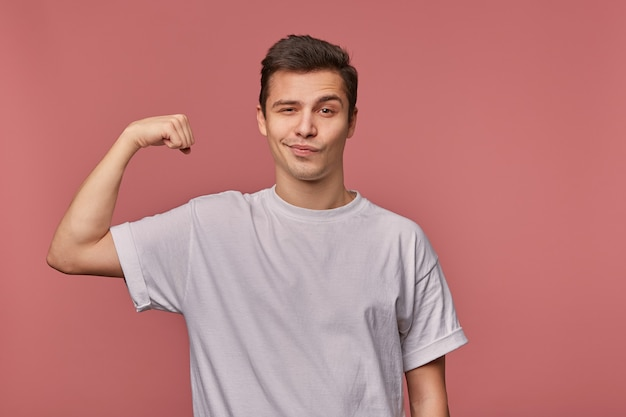 Portrait of young cheerful headsome guy wears in blank t-shirt, shows biceps, demonstrate power, stands on pink and broadly smiling.