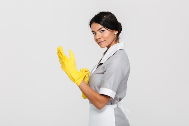 Portrait of young cheerful housekeeper wearing yellow rubber gloves while standing