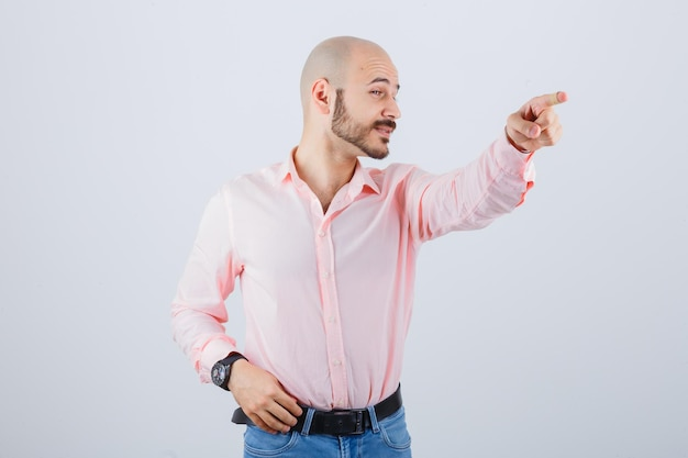 Portrait of a young cheerful man pointing away