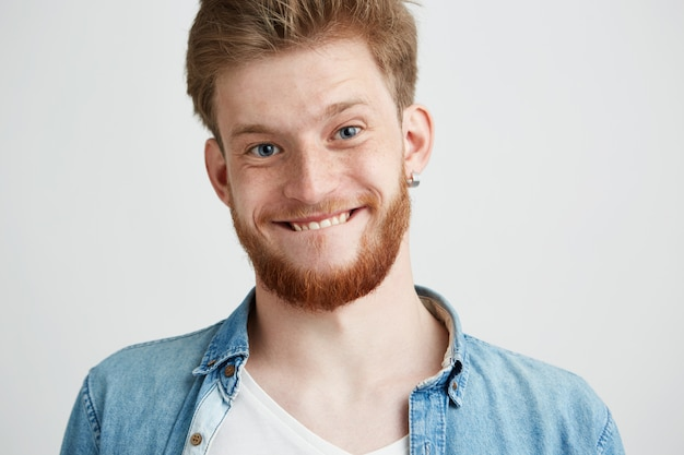 Portrait of young cheerful merry guy making funny face fooling.