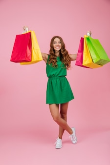 Portrait of young cheerful readhead curly woman in green dress, holding colourful shopping bags